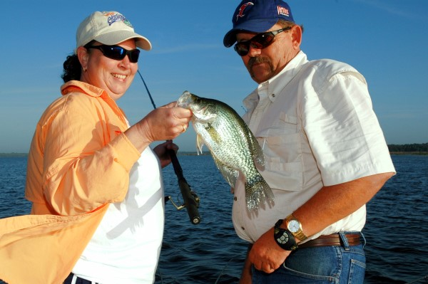 Baker looks on and admires a crappie caught by Kim Newton while fishing Orange Lake near Ocala, Florida.
