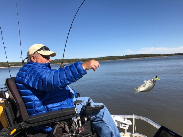 Swinging a crappie into the boat is part of the fun of any crappie trip. Here, Saldeen gets in on the fun.