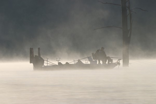 Silhouette of crappie fishermen spider rigging during an early morning fog