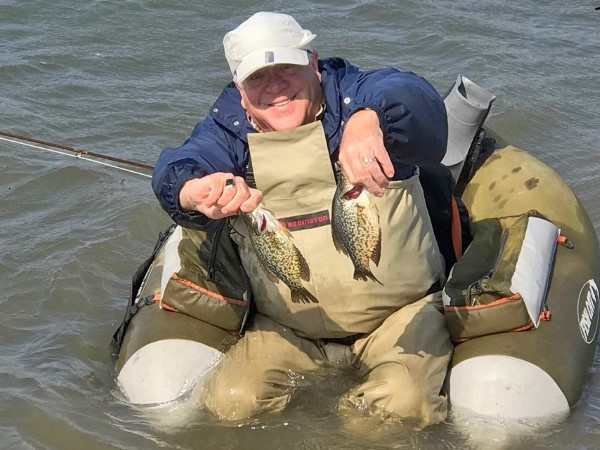 Bill Hartman displays two crappies he caught on back-to-back casts while fly fishing on a farm pond.